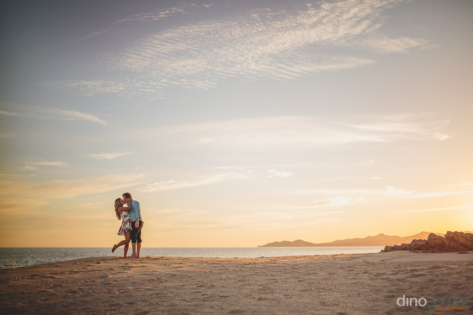 kissing on the beach at sunset in los cabos