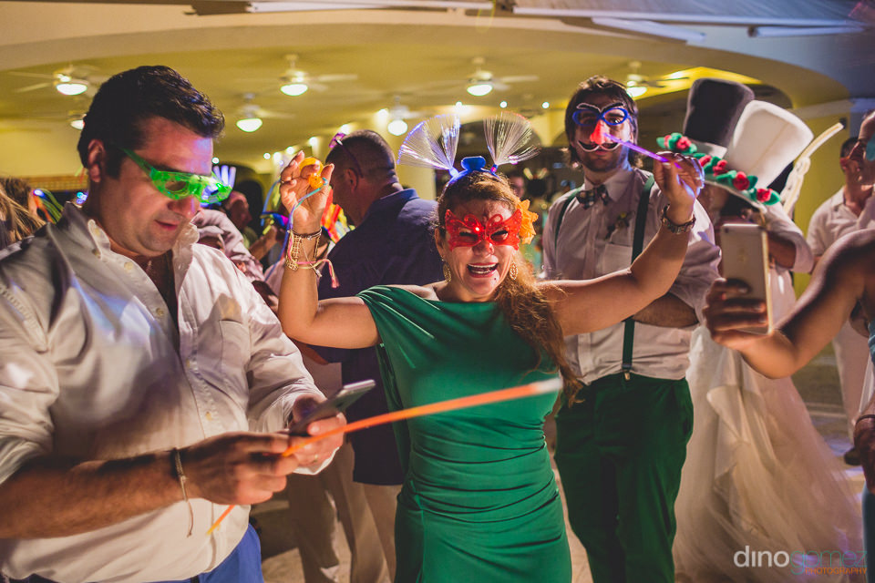 wedding guests wear masks and hold props during party
