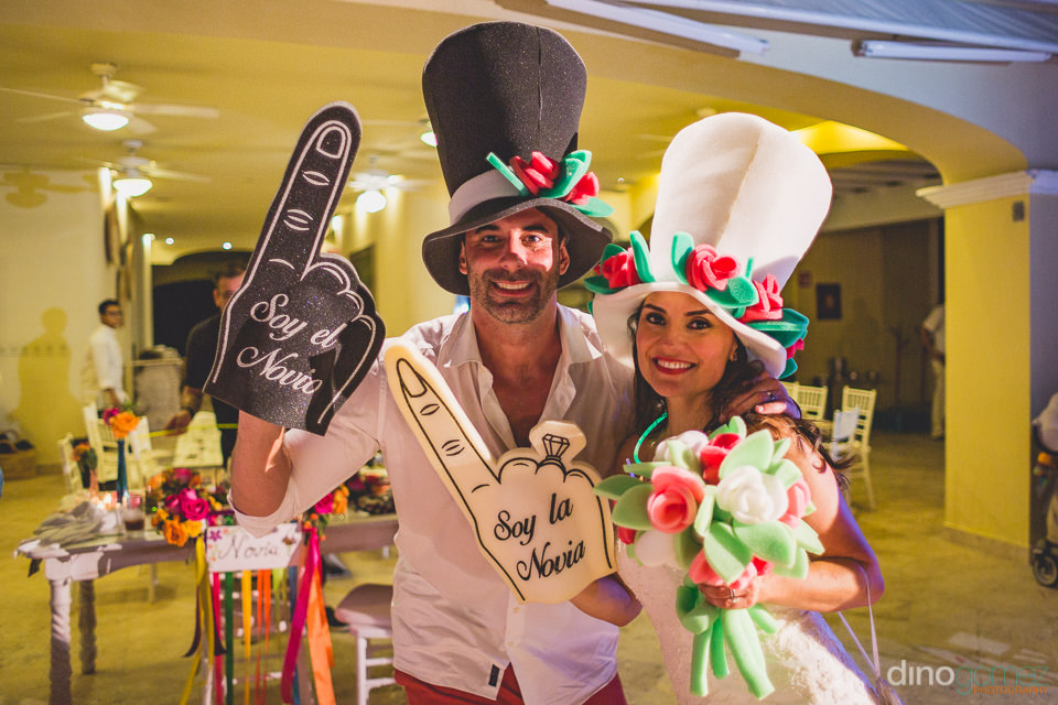 newlyweds wear big foam hands and hats during their wedding rece