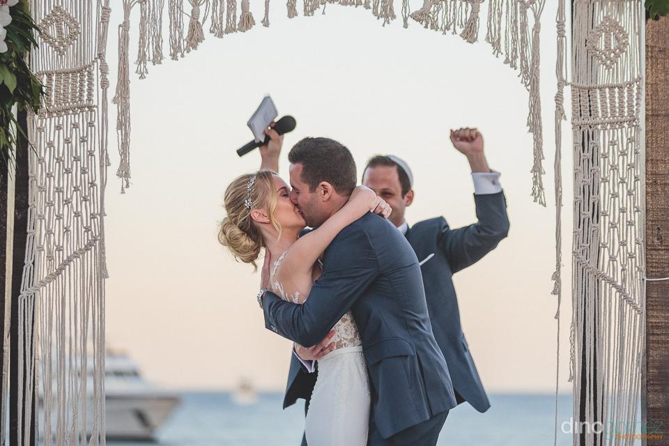 bride and groom kiss on medano beach in cabo san lucas