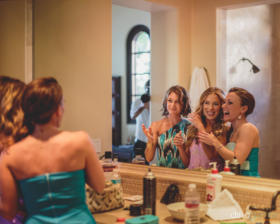 bride and bridesmaids doing makeup before wedding photographed b