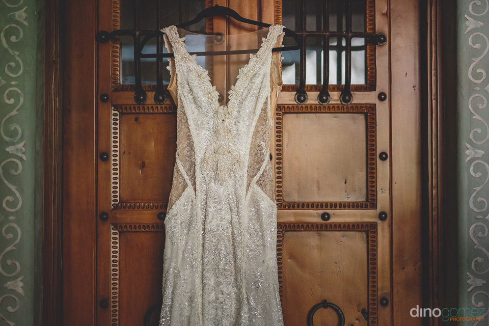white sleeveless wedding dress hanging in hotel room