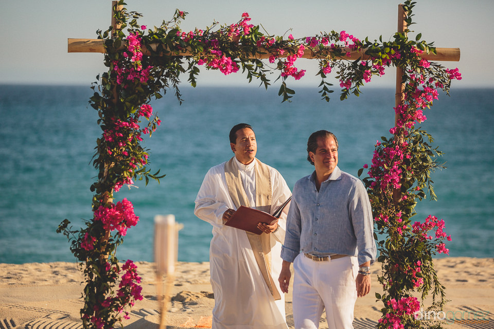 groom under beach chuppah waits for bride to join him