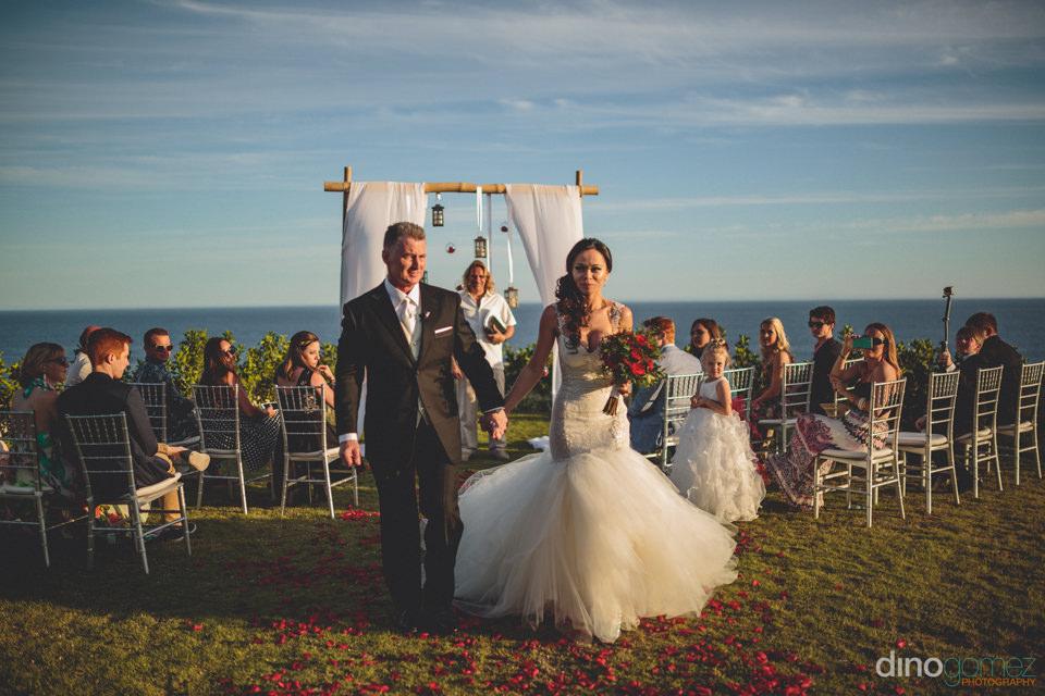 path of rose petals to altar overlooking pacific ocean wedding p