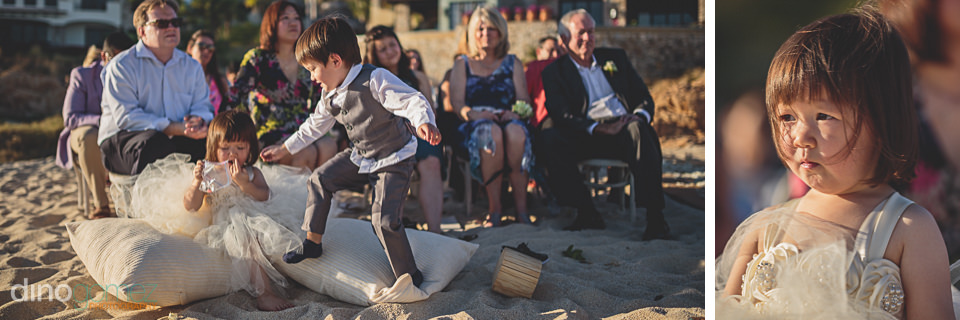 flower girl and page boy play in the sand during beach wedding i