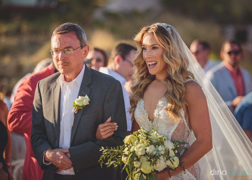 father walks his daughter down the aisle on her wedding day on t