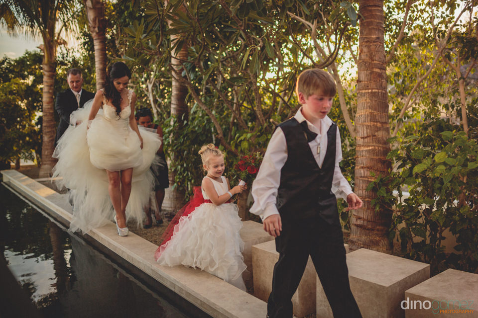newlyweds and family walk around pool at villa paradiso perduto