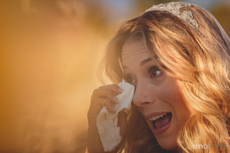 bride cries tears of joy during wedding ceremony on the beach