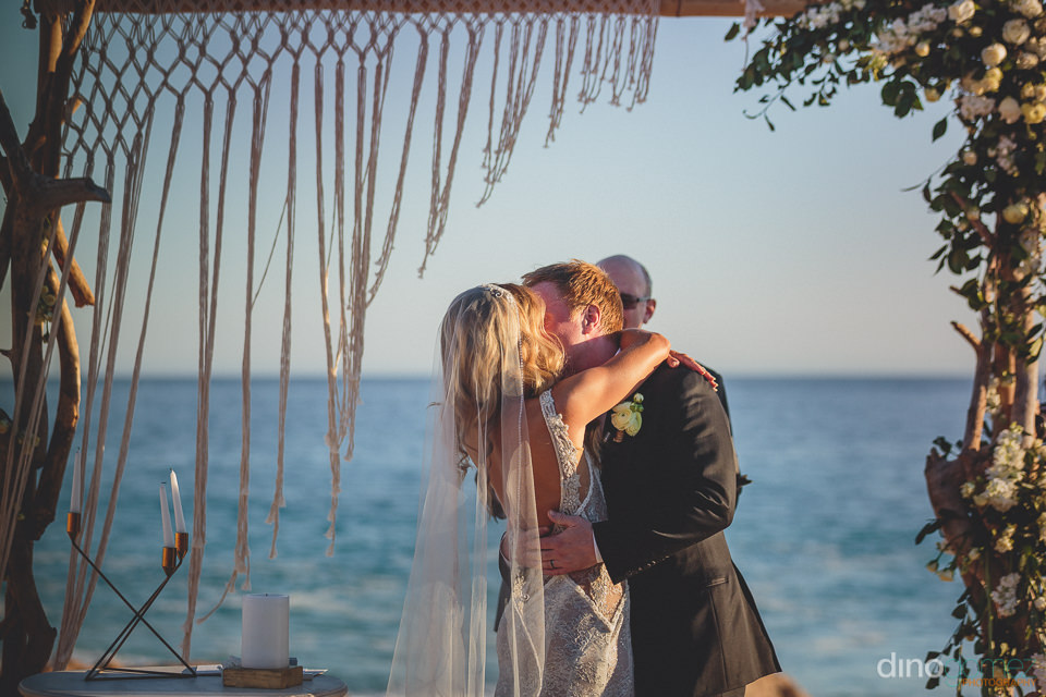 newlyweds kiss under flowery altar on the beach
