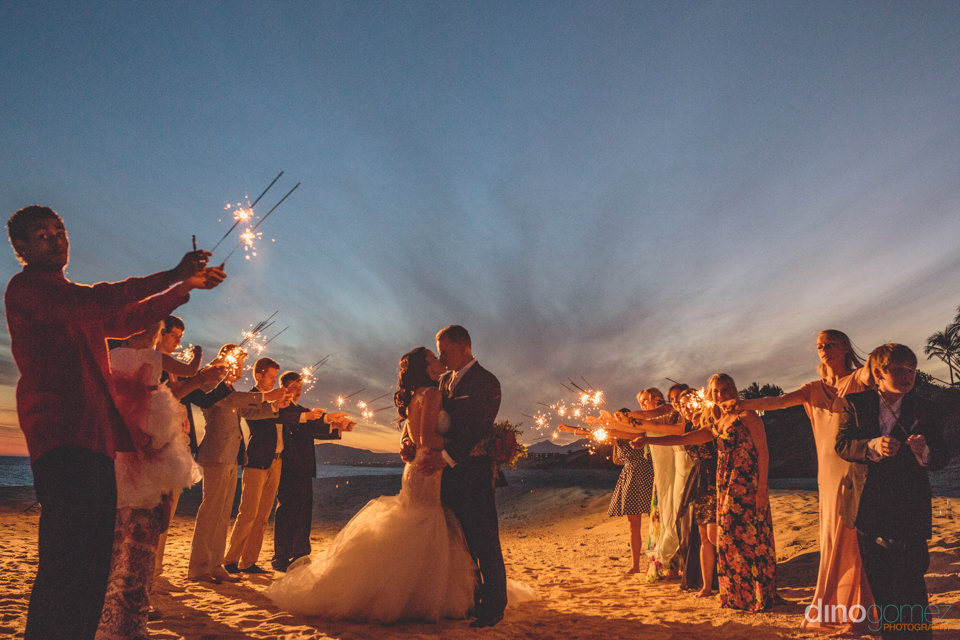 guests hold sparklers on the beach in cabo while newlyweds kiss