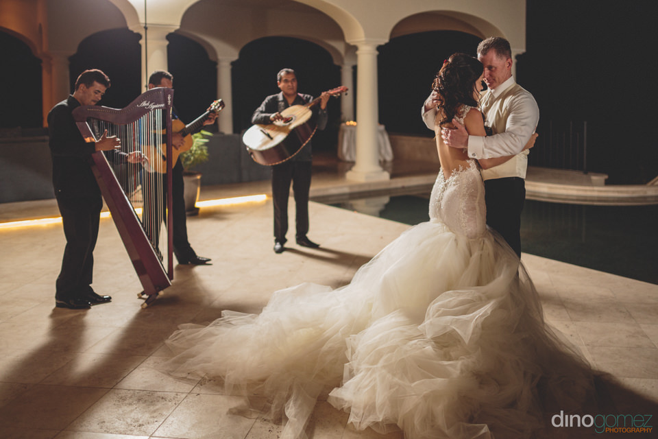 Newlyweds Dance Next To Three Piece Mexican Acoustic Band