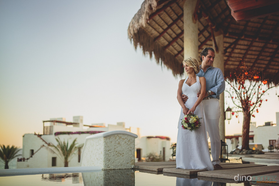 newlyweds stand by pool at las ventanas resort cabo in photo by