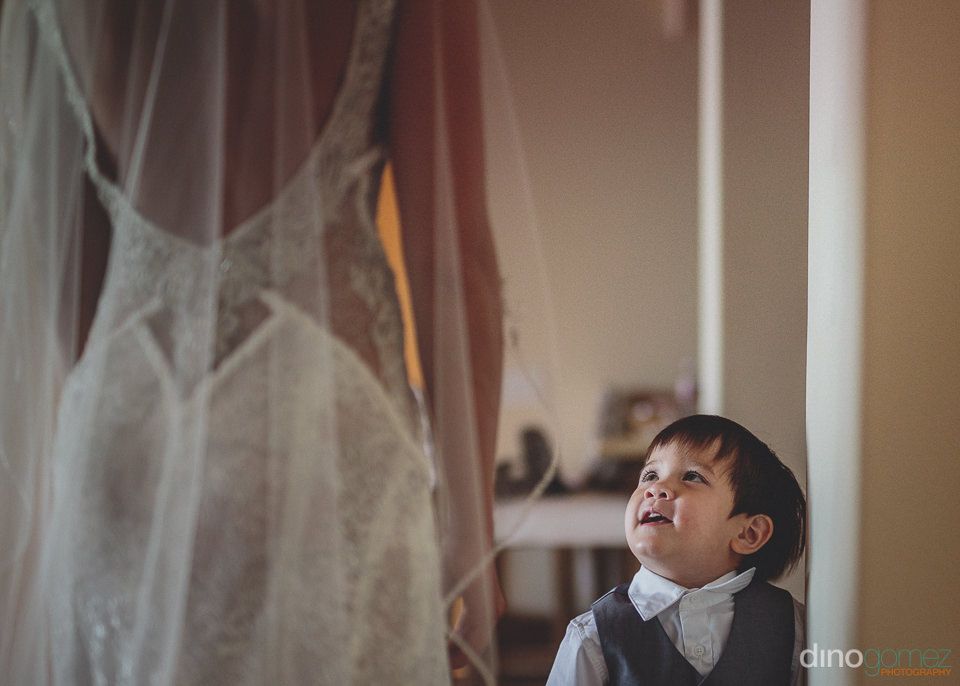 little boy looks at bride with smile on his face
