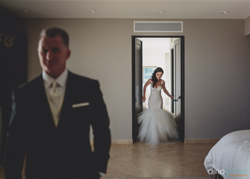 bride in wedding dress sneaks up on groom before the ceremony at