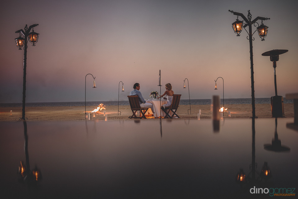 romantic beachside dinner with just the bride and groom photo by