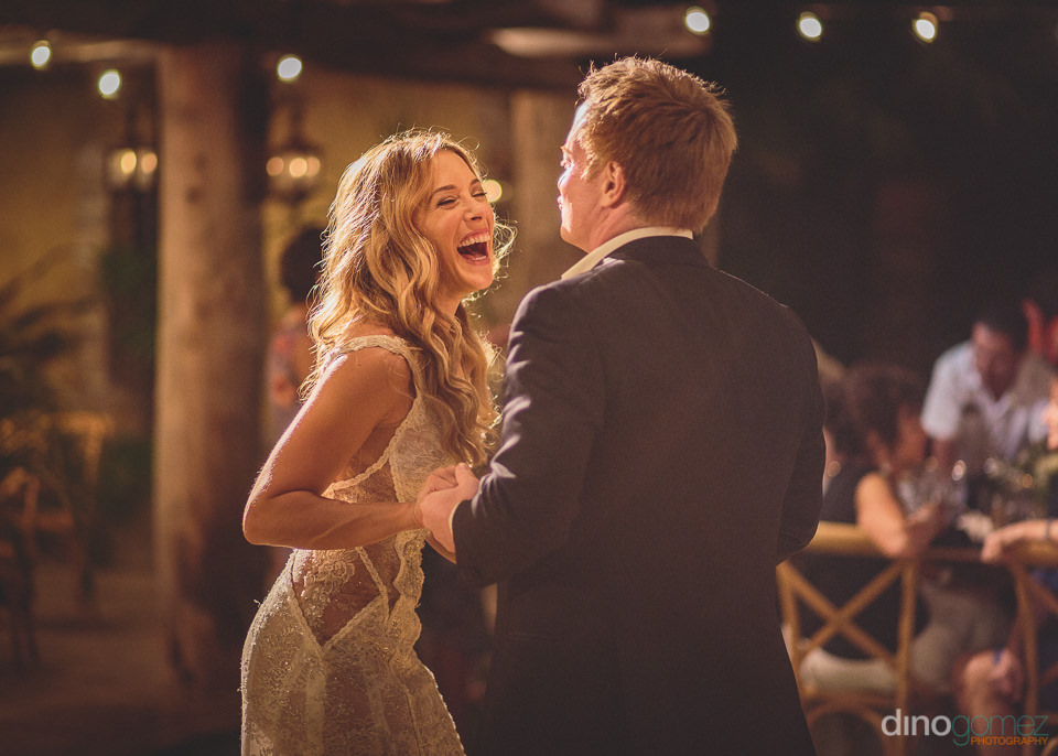 newlyweds smile and laugh on the dance floor at exclusive beach