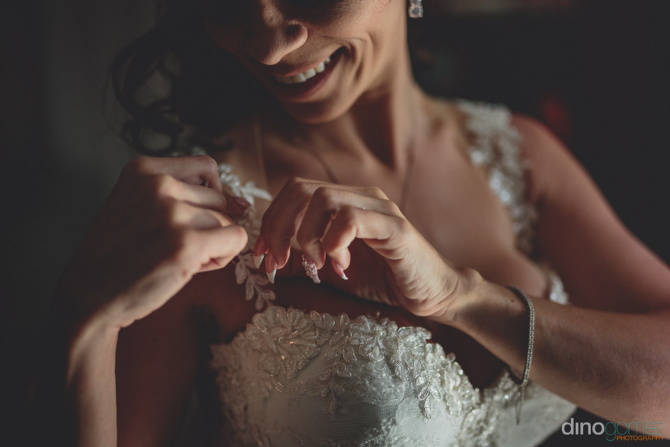 bride buttons the sleeves of her dress before private luxury wed