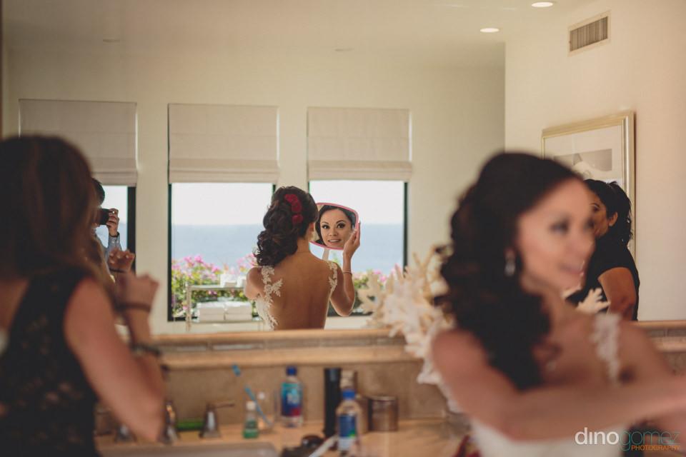 unique wedding photo of bride looking into a mirror on her weddi