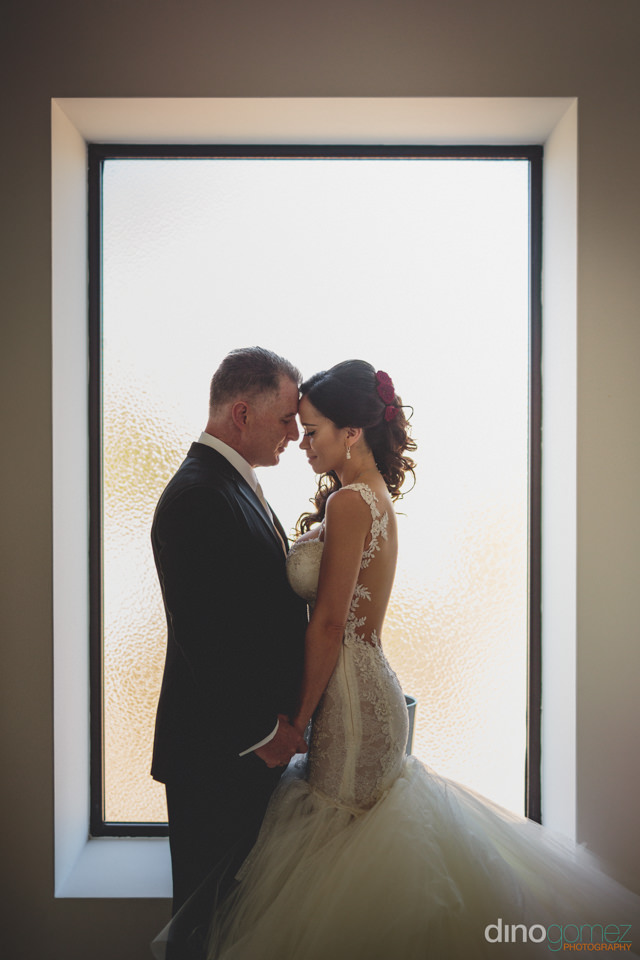 wedding photo of bride and groom standing in front of white wind