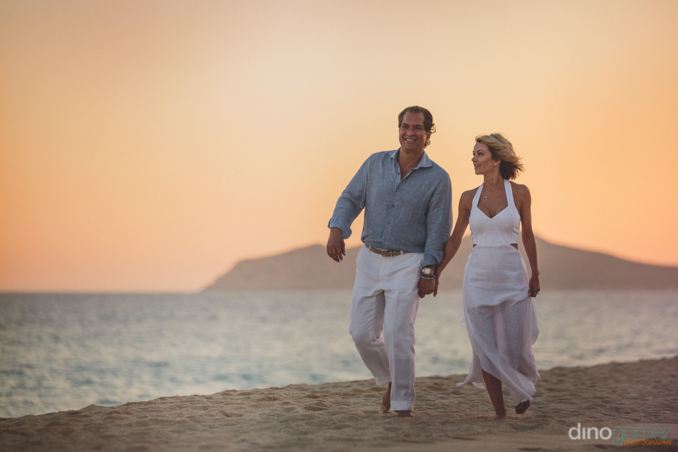 husband and wife take sunset walk on the beach of las ventanas h