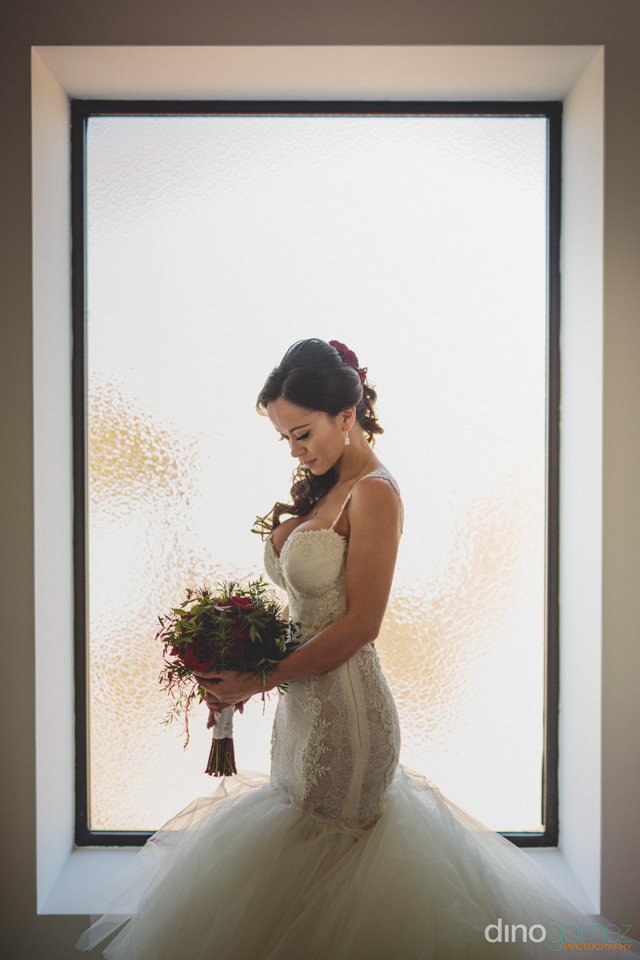 beautiful bride holds red rose bouquet wedding photo by dino gom