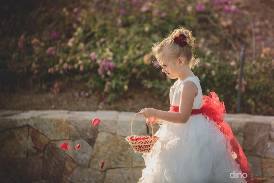 flower girl throwing red rose petals at destination wedding cere