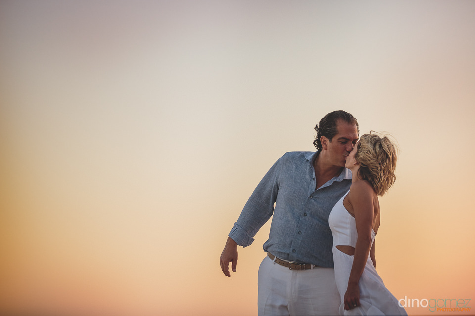 sunset beachside kiss after intimate wedding in los cabos mexico
