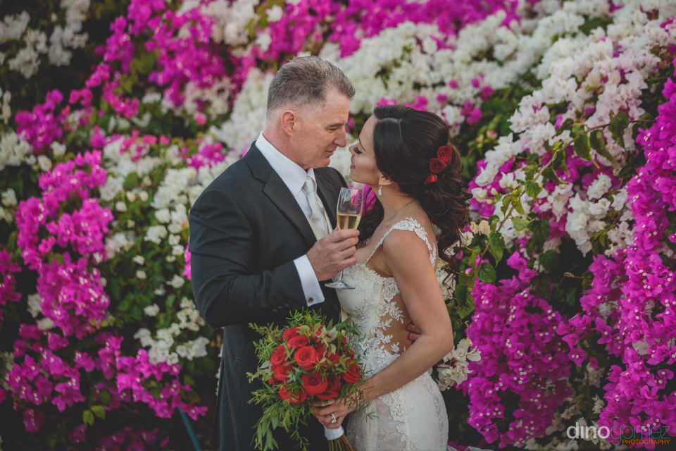 Groom Holding Champagne And Bride In Front Of White And Lavender
