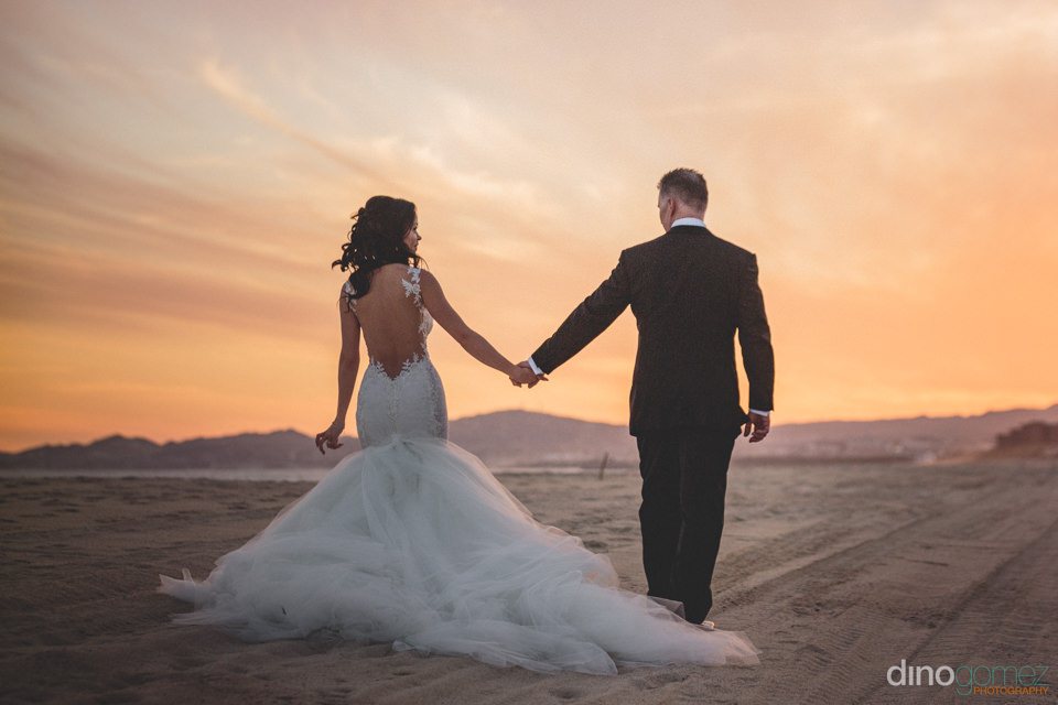 Newly Married Husband And Wife Hold Hands And Walk Into The Suns