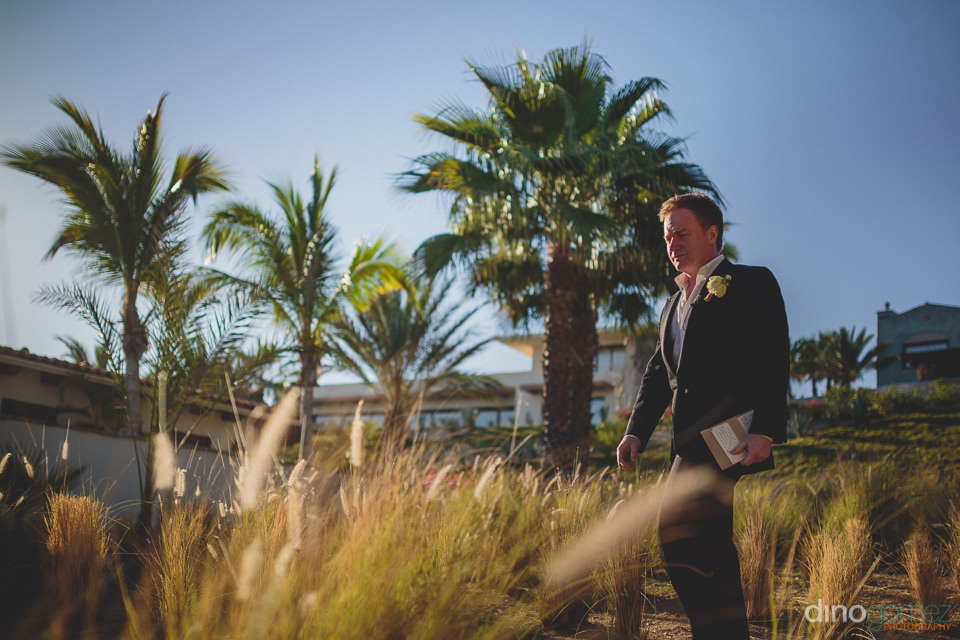 groom walking to the wedding altar on the beach in los cabos pho
