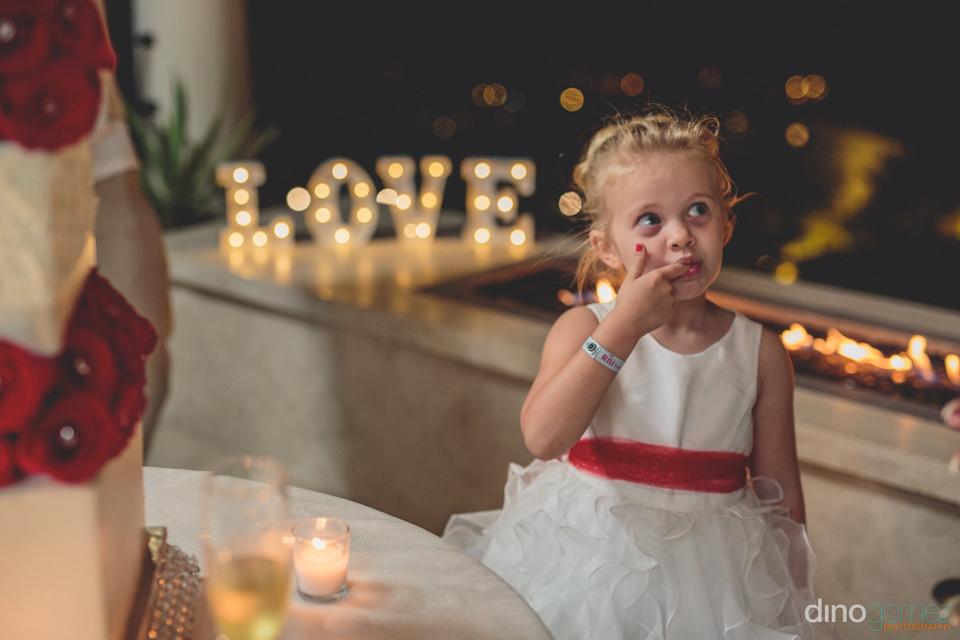 flower girl eats wedding cake in los cabos mexico