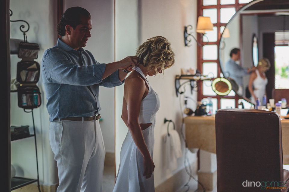 groom buttons up the dress of the bride before beach wedding in