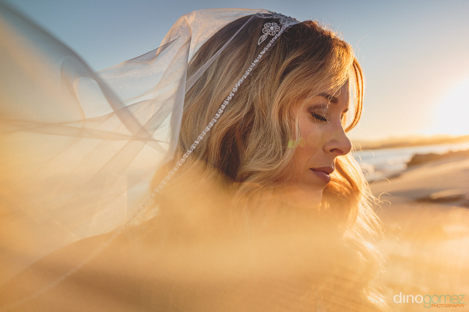 closeup photo of stunning bride with veil flowing in the wind