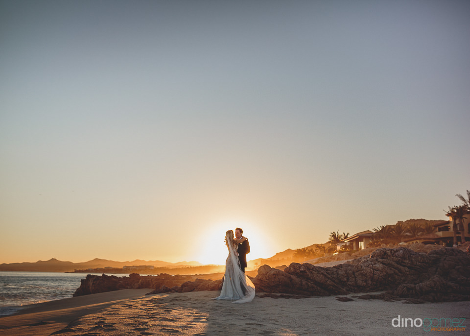 newlyweds silhouette against setting sun in los cabos photo by d