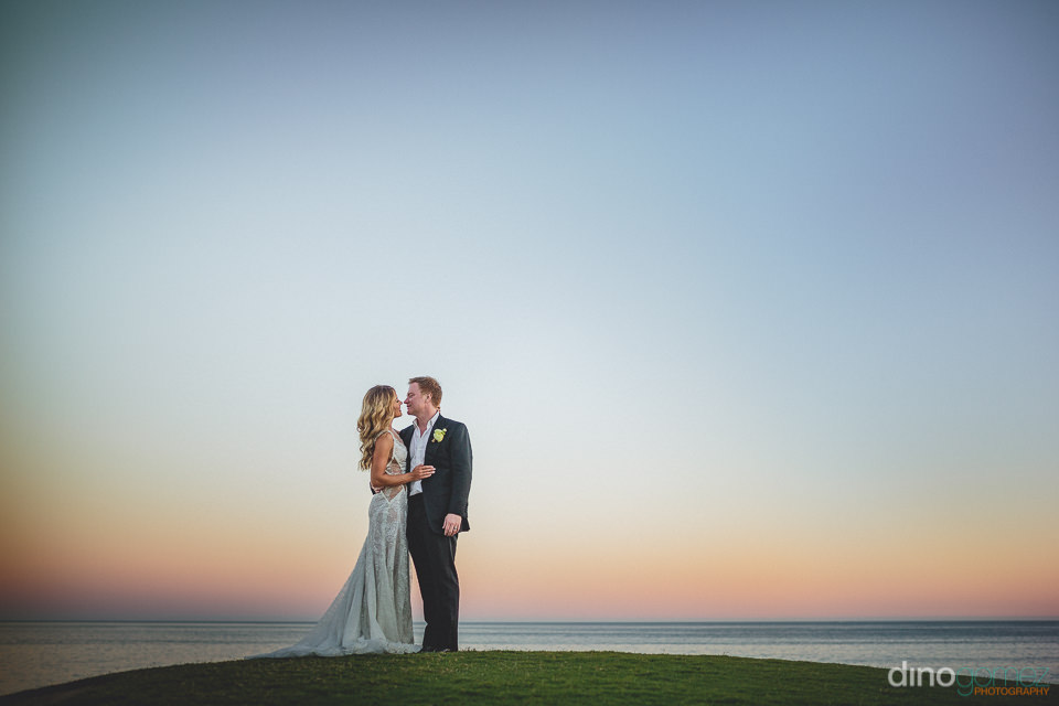 groom with arm around bride on their wedding day by the ocean in