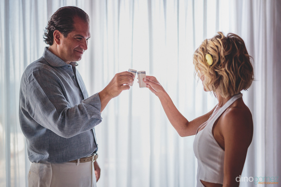 bride and groom drink tequila shot before wedding in cabo mexico