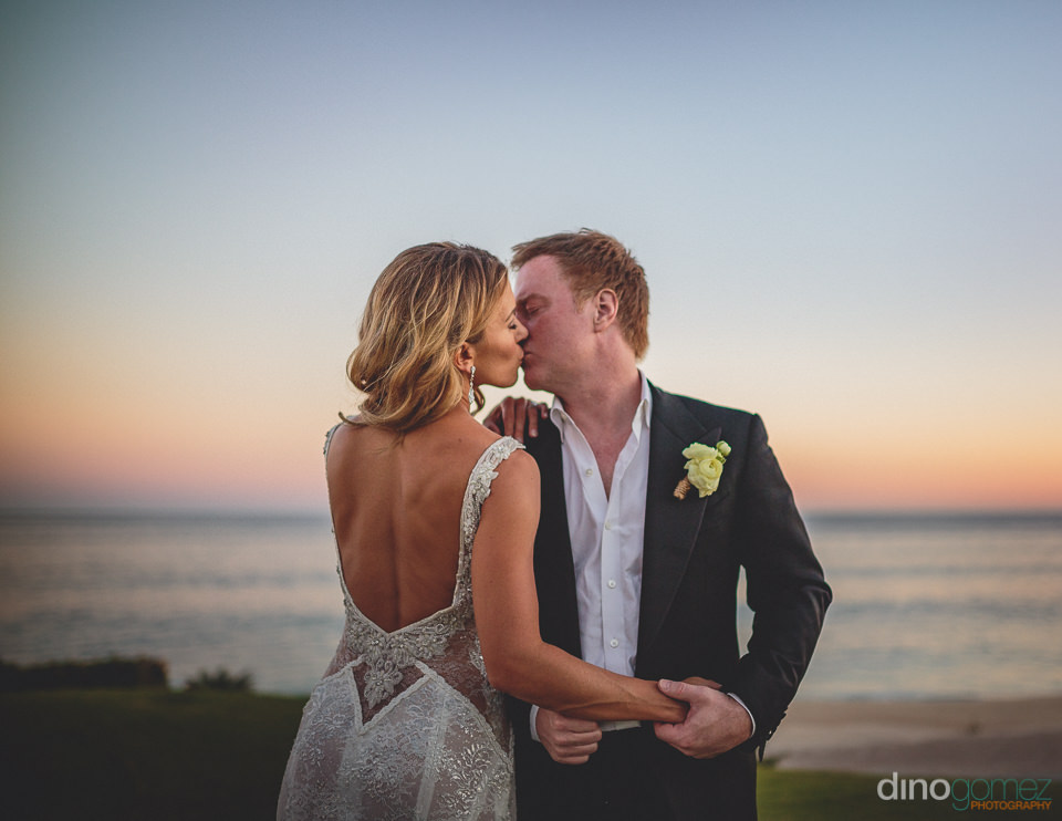 newlyweds kiss at beachside golf course in los cabos mexico