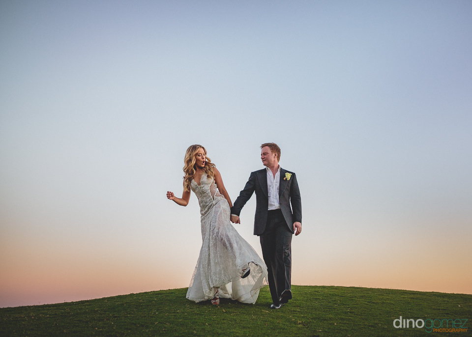 newlyweds walk together across golf course in cabo san lucas mex