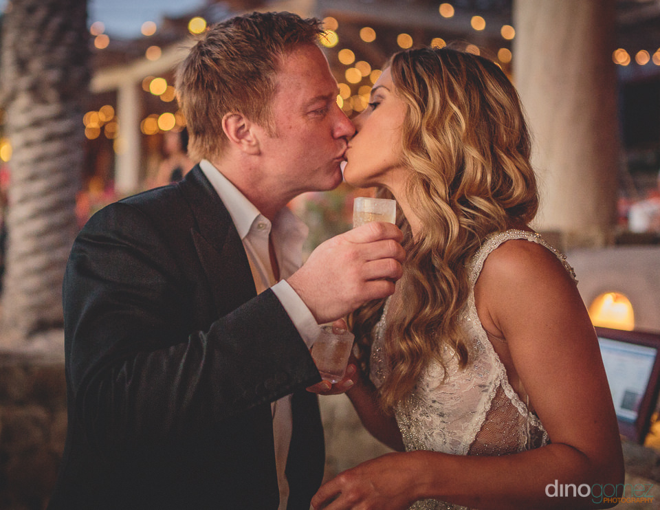 kissing newlyweds hold shots of tequila in wedding photo by dino