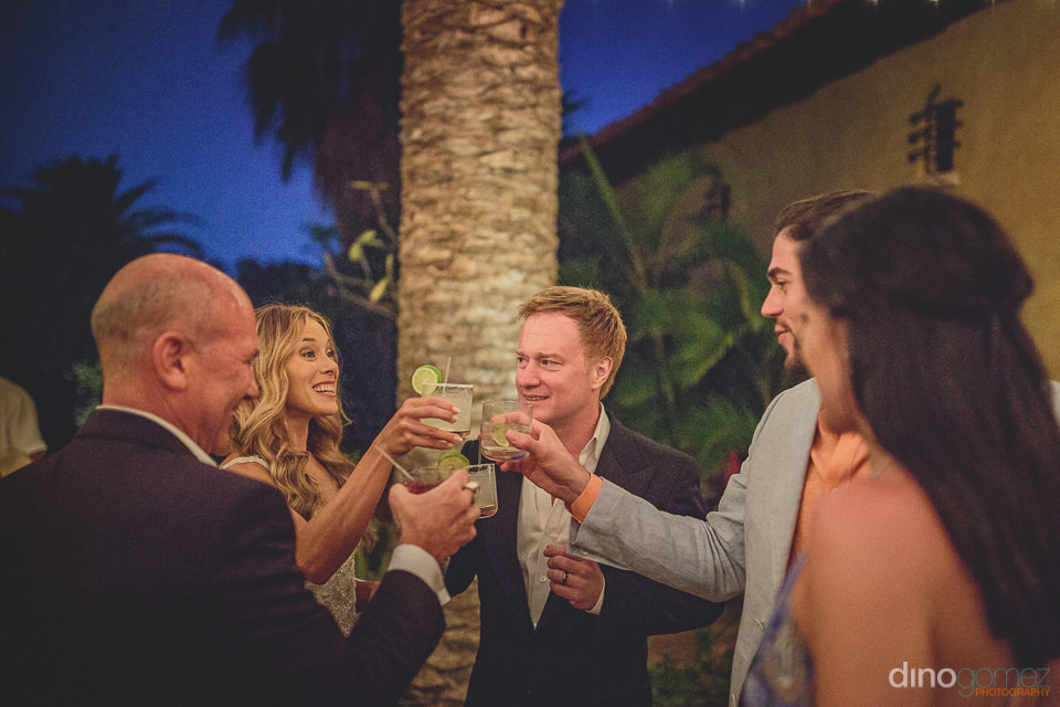 wedding guests toast the bride and groom at reception in cabo sa