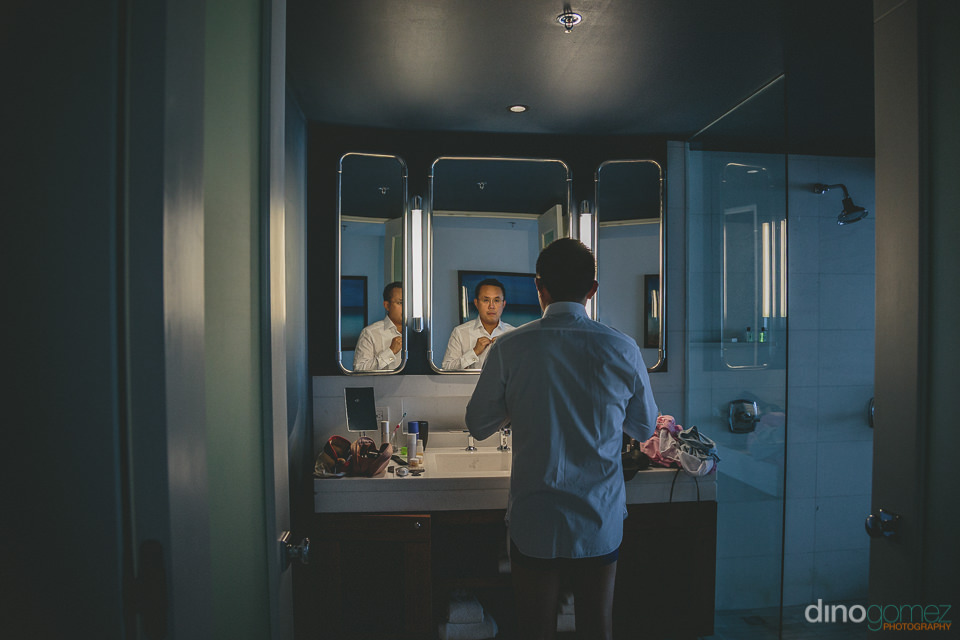 groom dressing looking into bathroom mirror at the cape a thomps