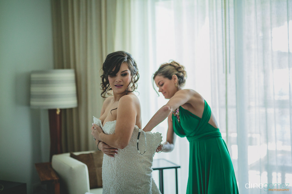 bridesmaid helps bride put on wedding dress