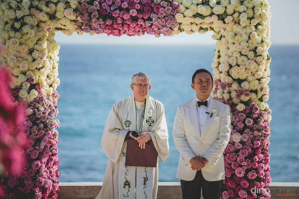 groom and priest under white and purple rose altar on the beach