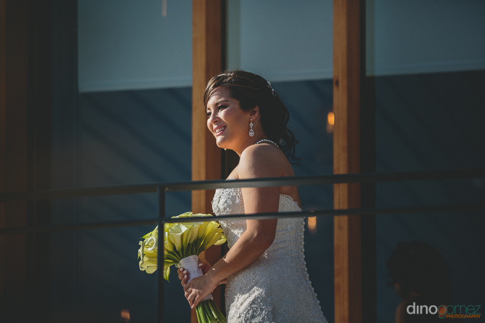 bride holding bouquet looks happily at the wedding ceremony