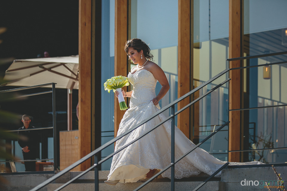 bride walks down stairs to wedding ceremony overlooking the ocea