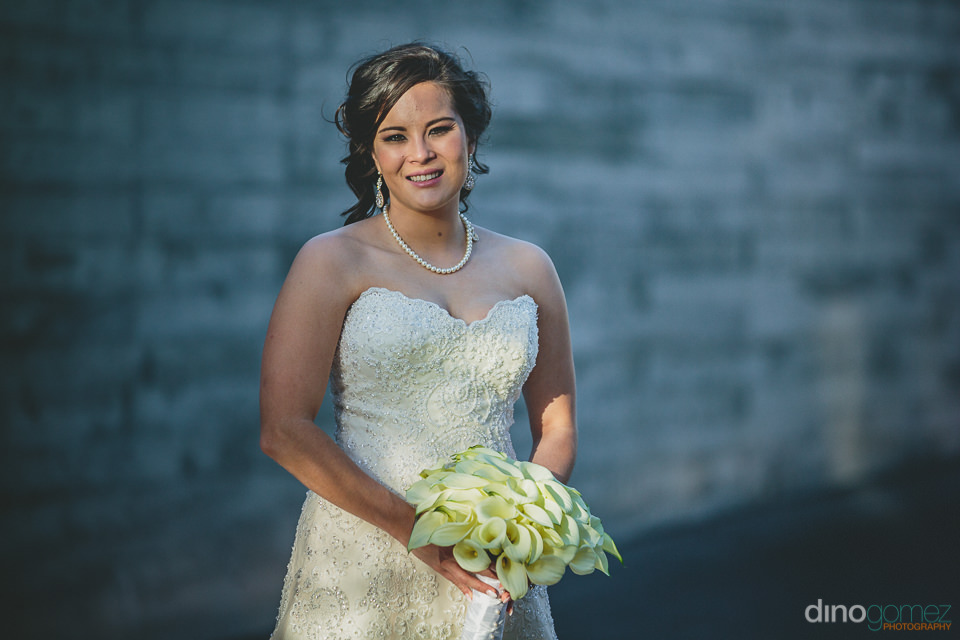 photo of the bride by herself holding her bouquet