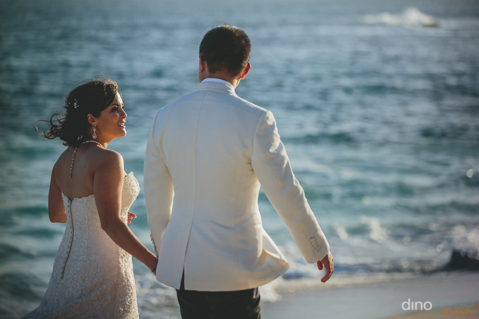 newlywed couple walk hand in hand on misiones beach cabo