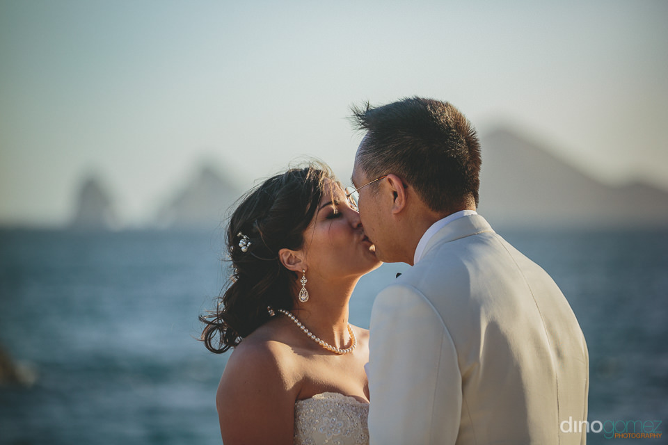 kissing on the beach in cabo during destination wedding