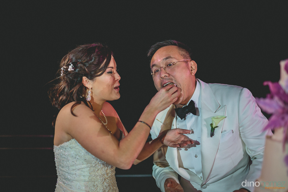 bride feeds groom piece of wedding cake