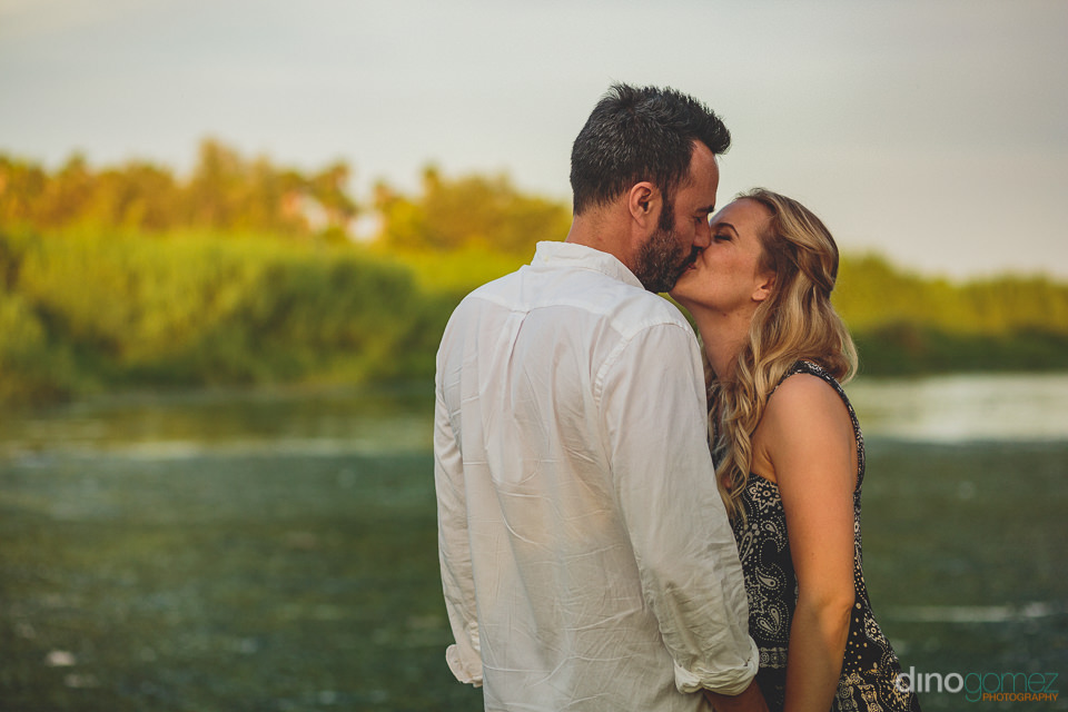 newlyweds kiss during engagement photo session with cabo photogr